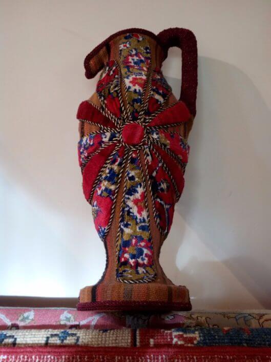 Anfora in terra cotta ricoperto con tappeto e kilim. Provenienza: Persia.